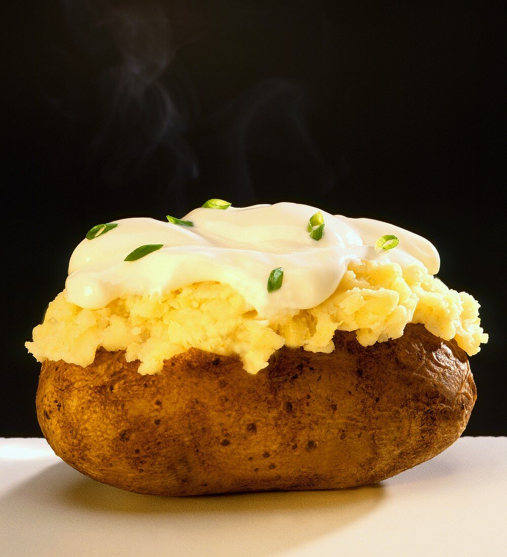 A Steaming Baked Potato with Sour Cream and Chives