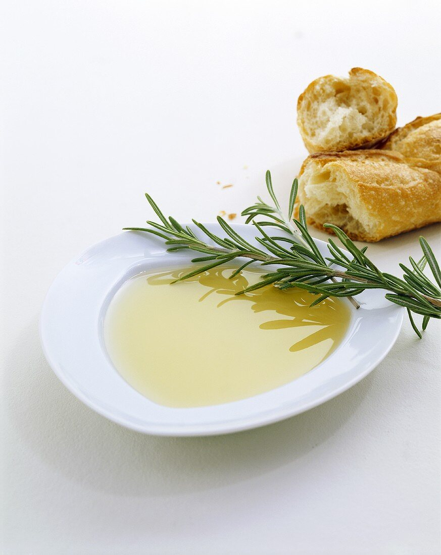 Olive oil on plate with rosemary and baguette