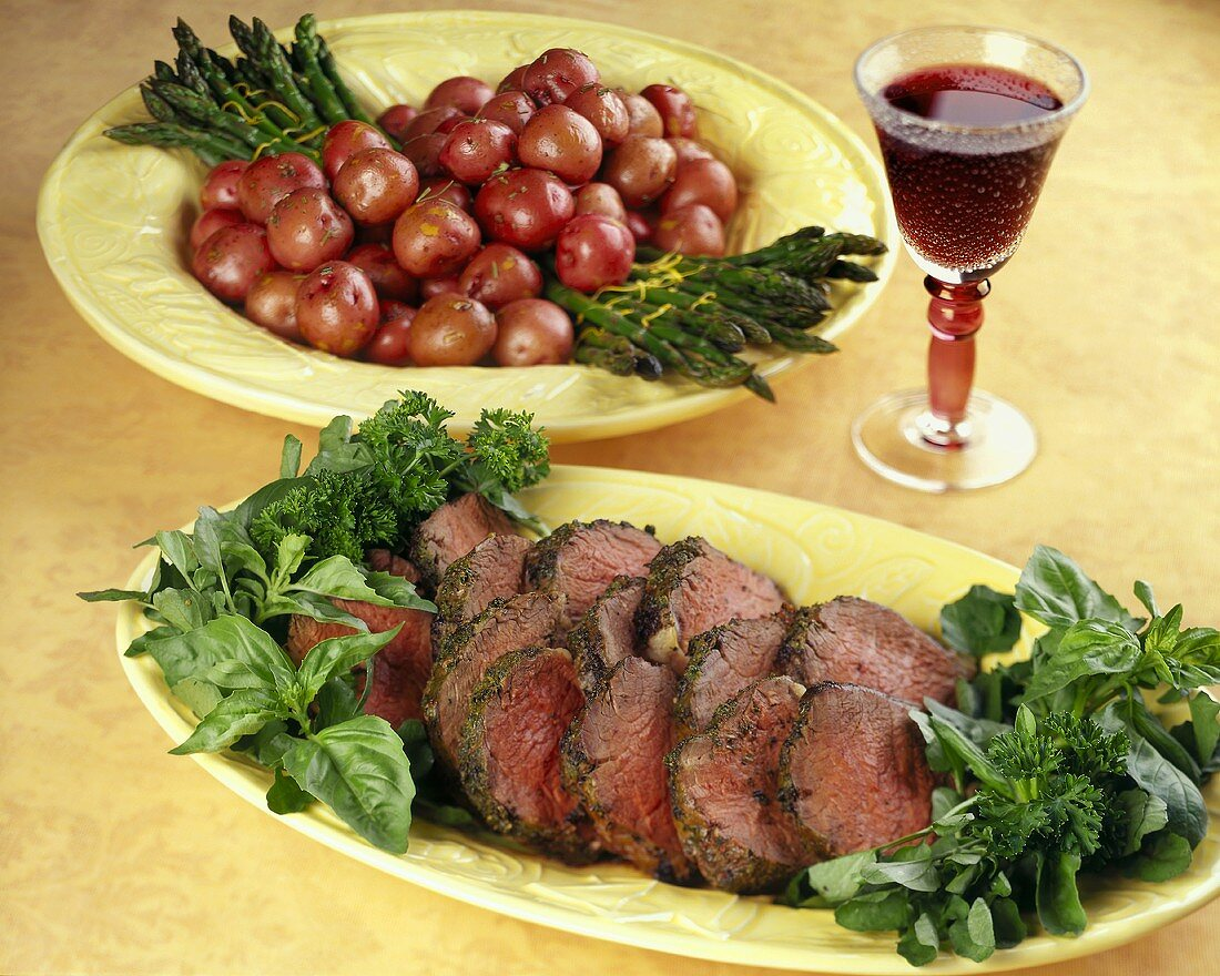 Sliced Herbed Roast Beef on Platter; Red Potatoes and Asparagus