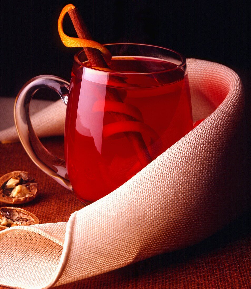 Hot Cranberry Juice in a Glass Mug with a Cinnamon Stick