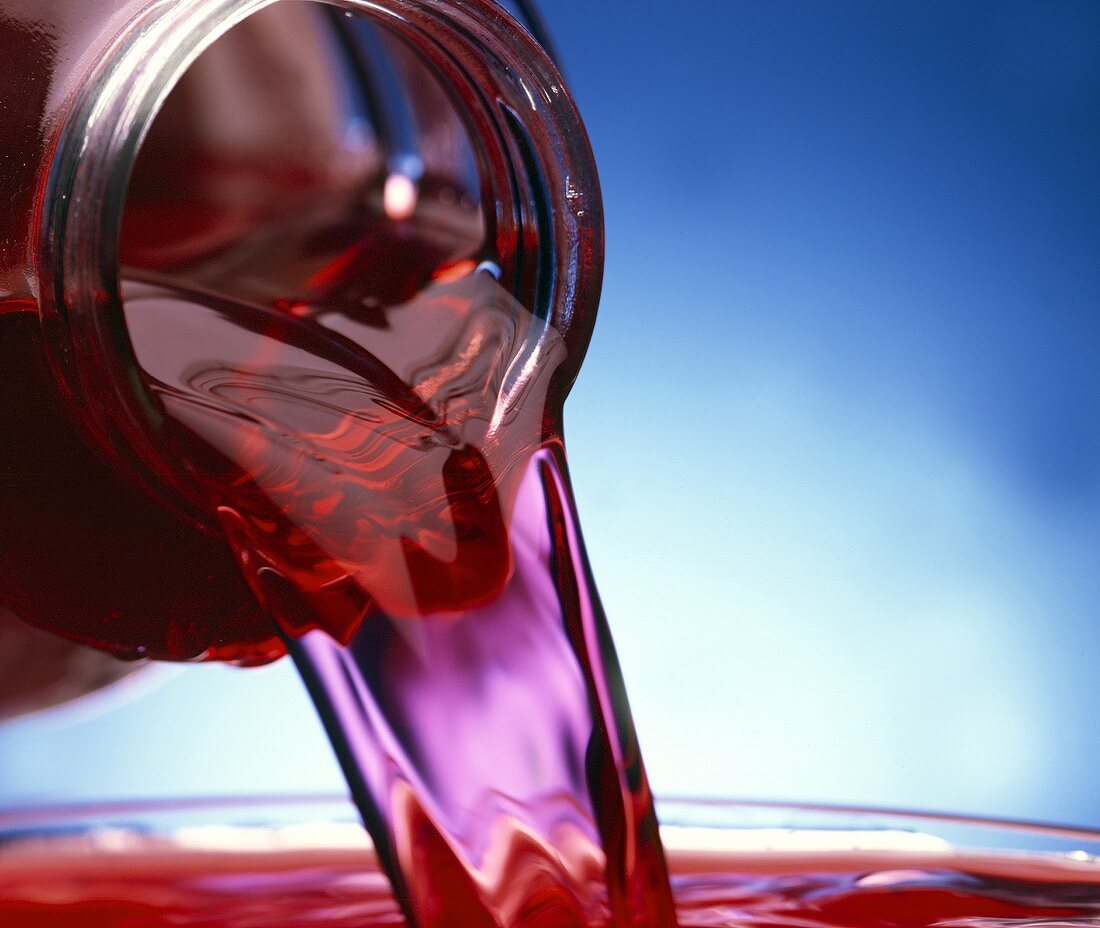 Pouring cranberry juice out of bottle