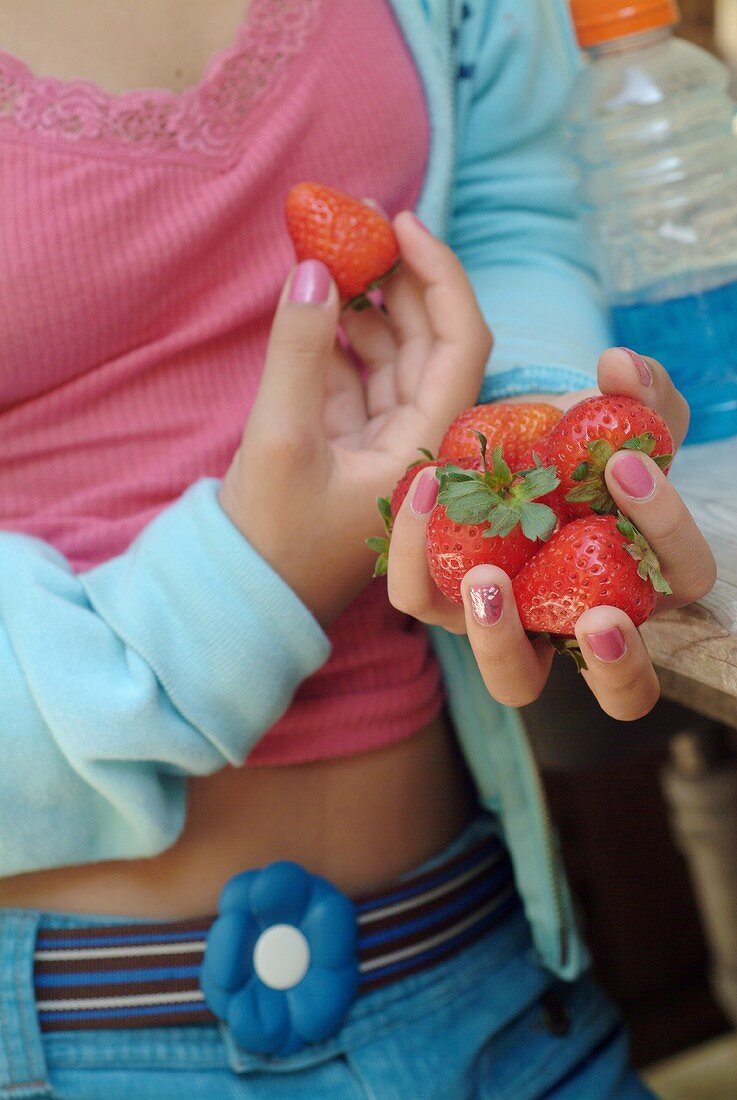 A Girl Holding a Strawberry