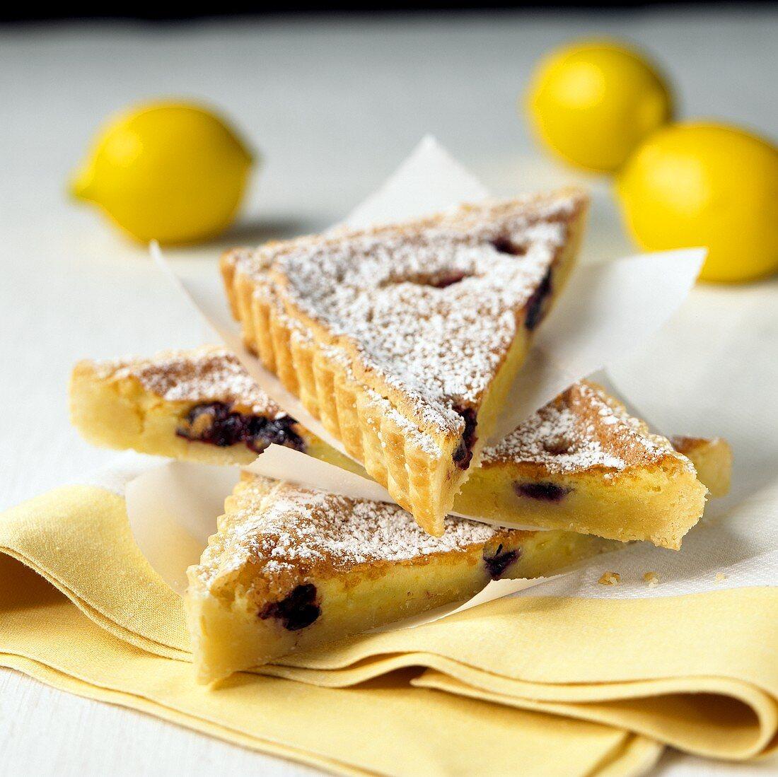 Lemon and blueberry tart cut into triangular pieces