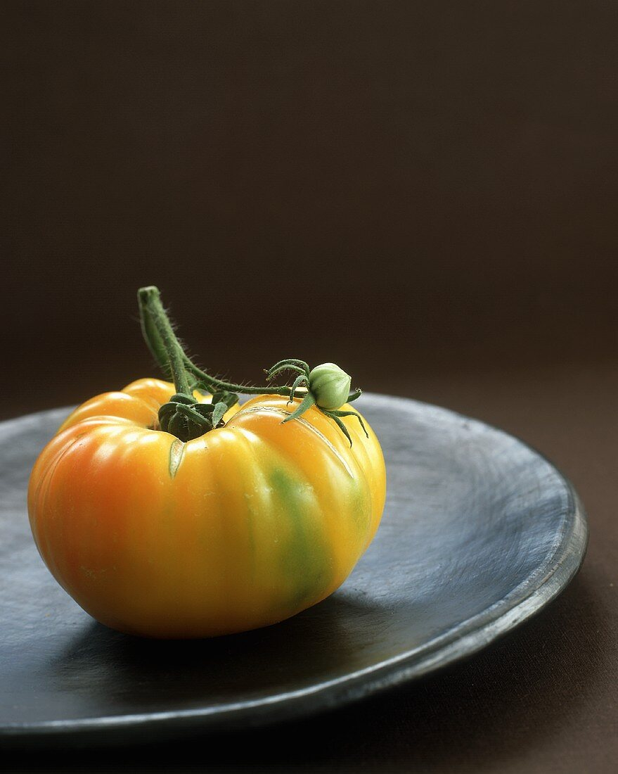 A Yellow Tomato on a Black Plate