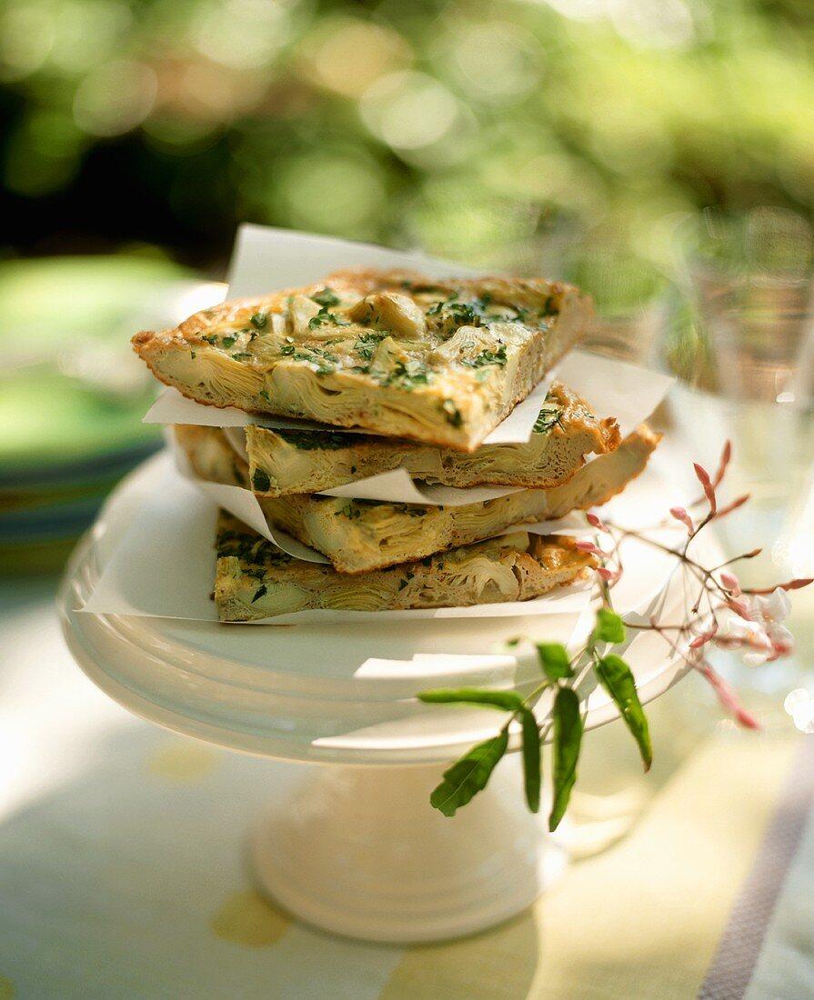 Slices of Artichoke Frittata on a Pedestal Dish Outside