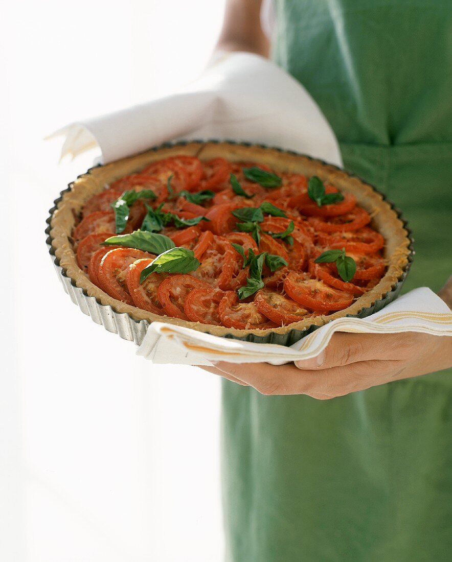 Woman serving tomato tart with basil in the baking dish