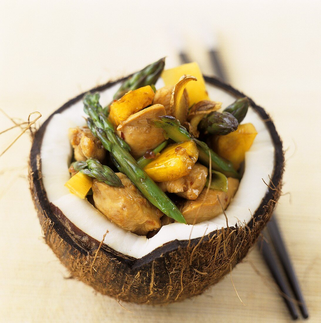 Sweet and sour chicken ragout in hollowed-out coconut
