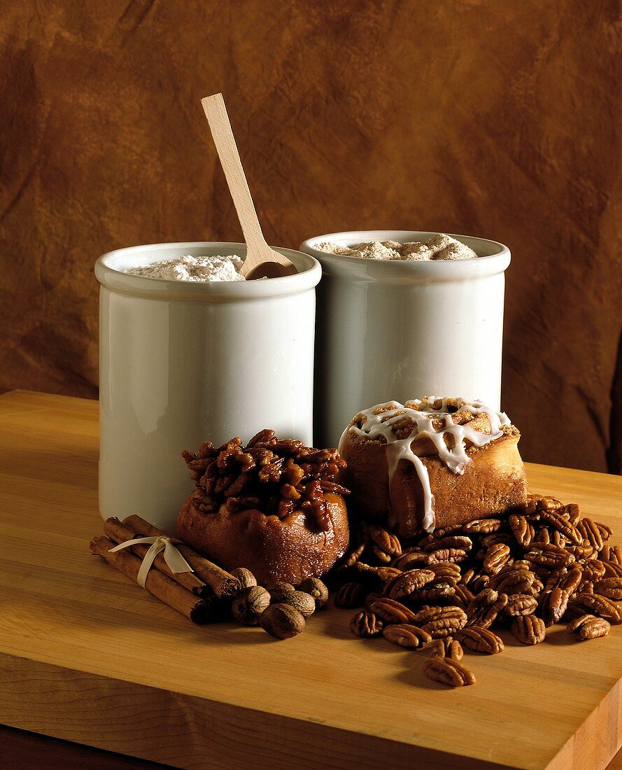 Sticky buns with pecans and cinnamon sticks; flour in tins