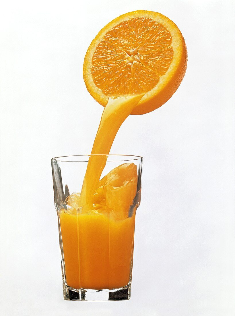Orange Juice Pouring From Orange Half into a Glass