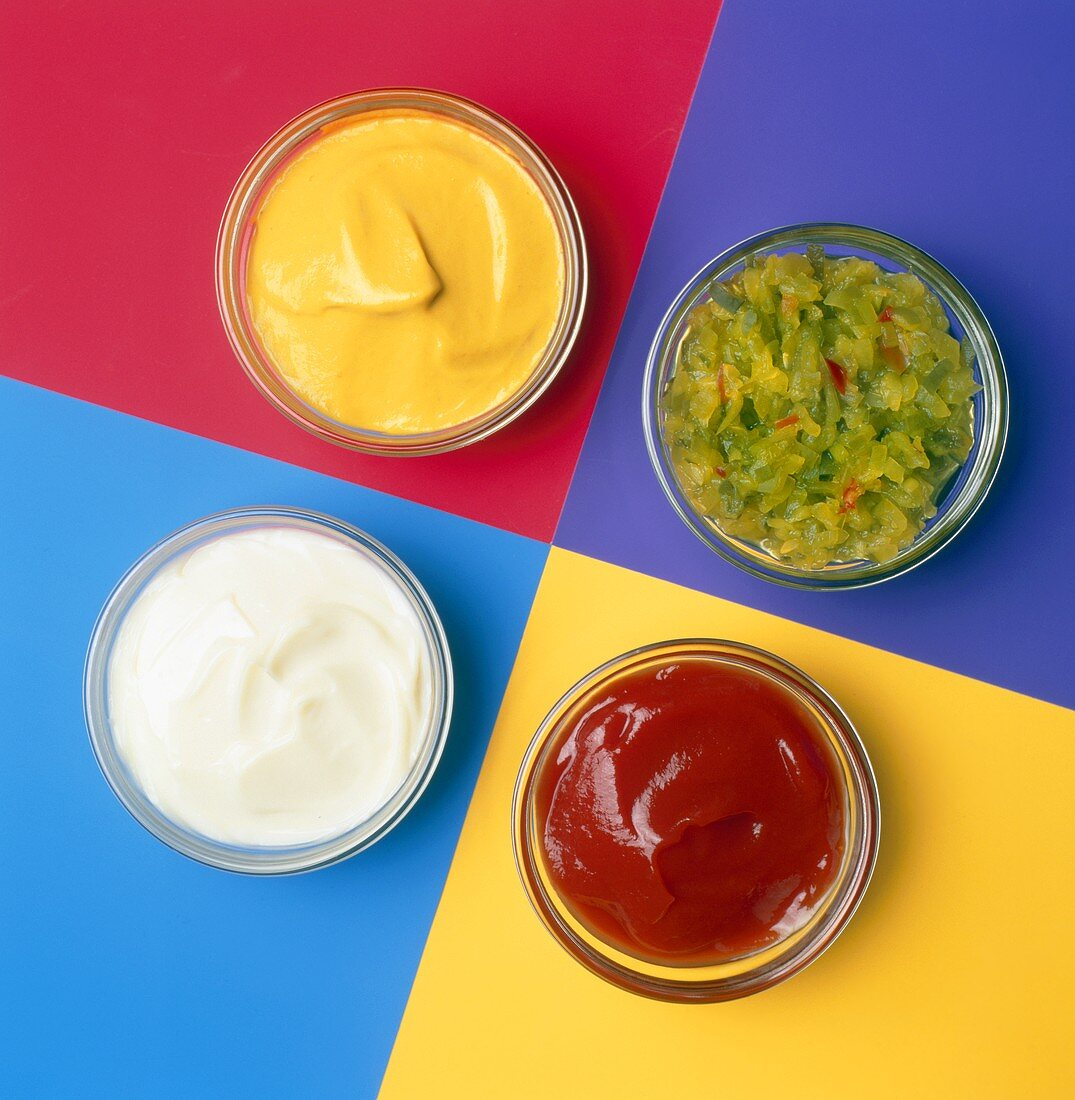 Assorted Condiments in Four Glass Bowls on Colored Squares