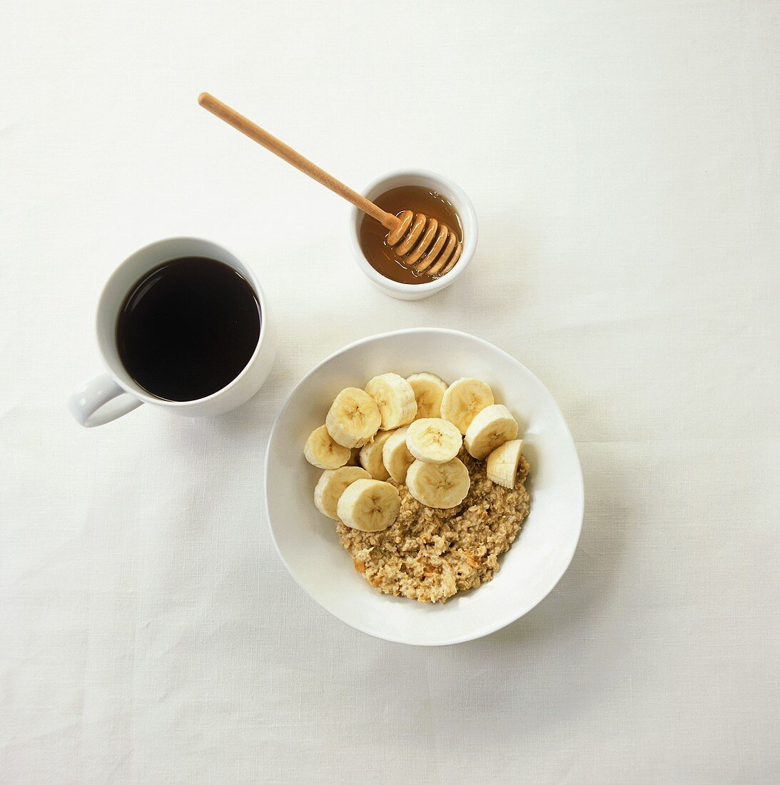 Muesli with bananas, honey and cup of black coffee
