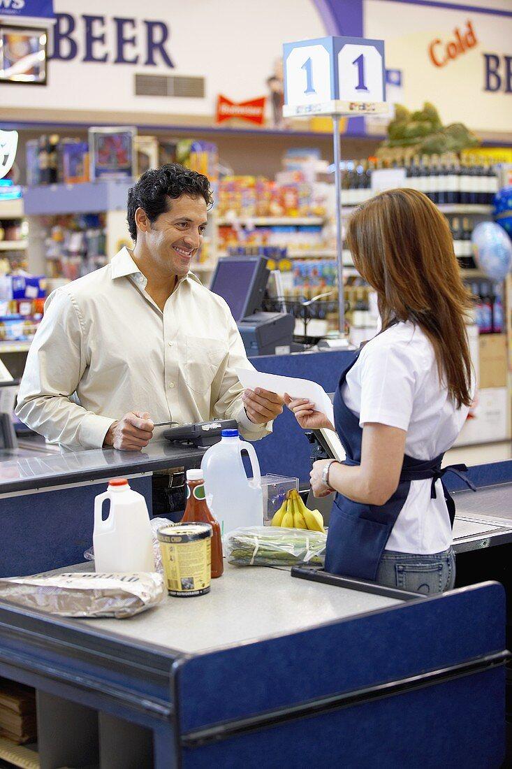 Supermarket check-out girl handing customer till receipt