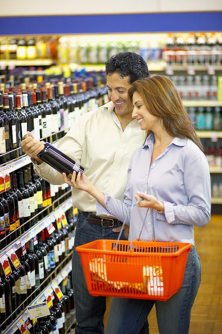 Man and woman buying wine in a supermarket
