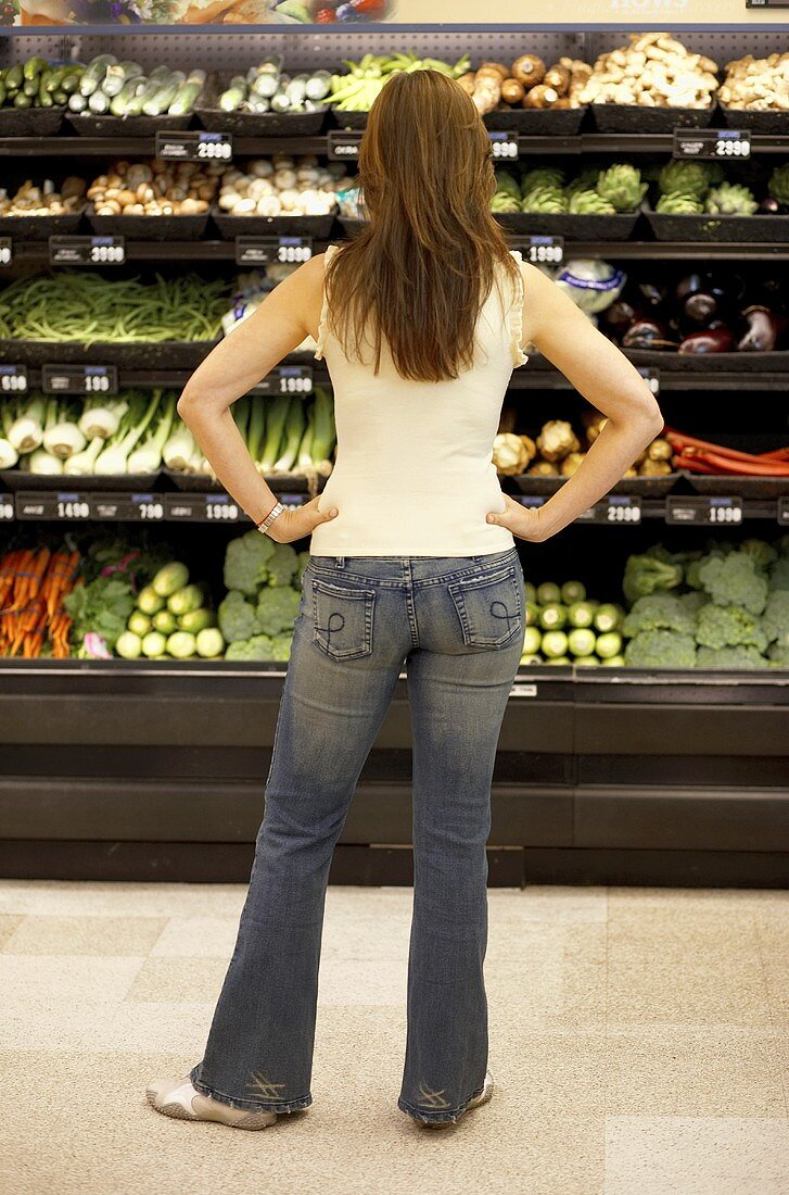 Woman with Hands on Her Hips Looking at Vegetables in Produce Department of Supermarket