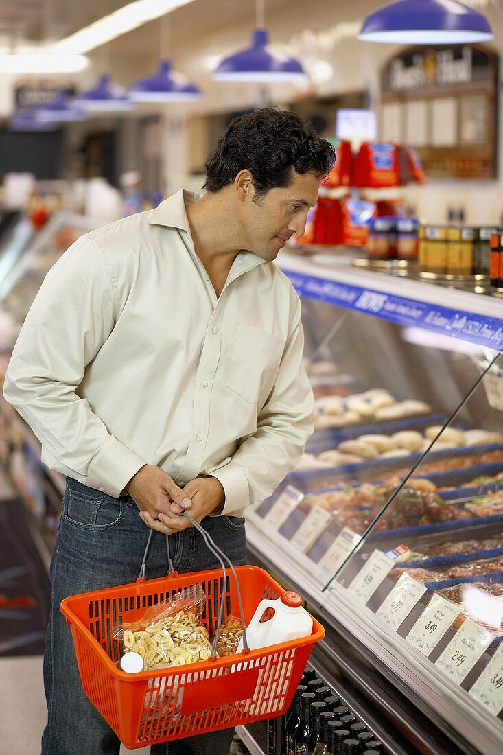 Man with basket in the meat department of a supermarket