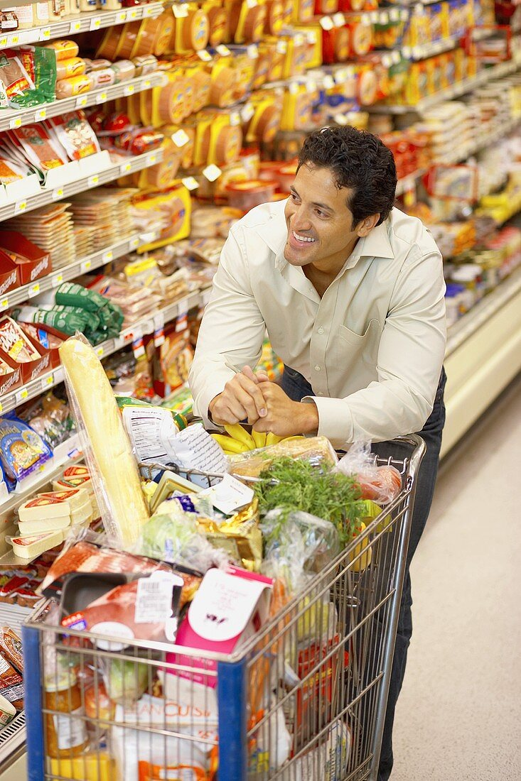 Smiling man with full shopping trolley in a supermarket