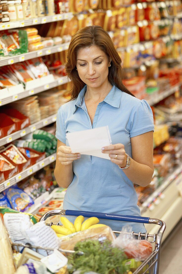 Woman reading shopping list in a supermarket