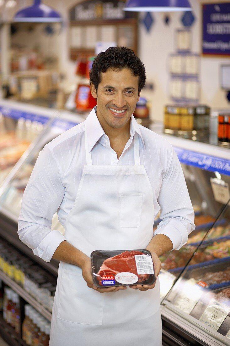 Butcher showing steak in packaging in a supermarket