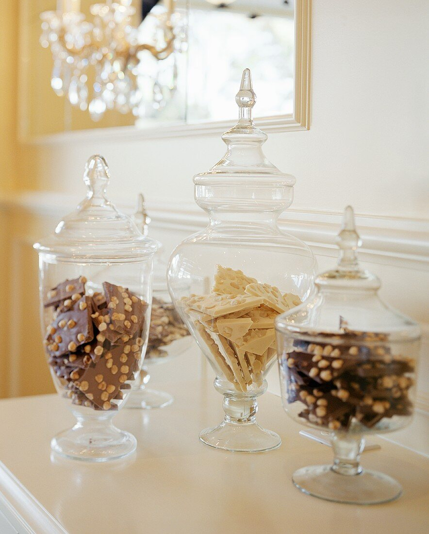 Sweets in glass containers on chest of drawers