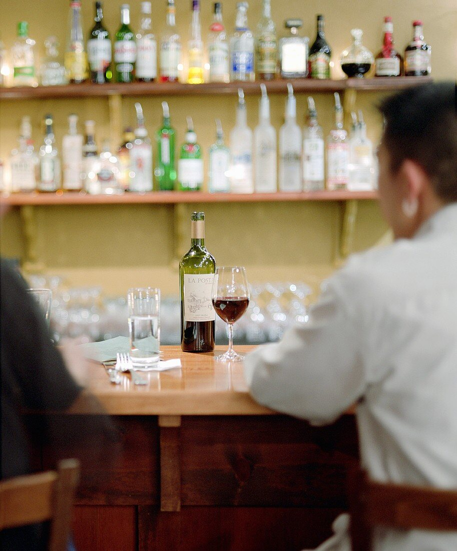People drinking red wine at a bar counter