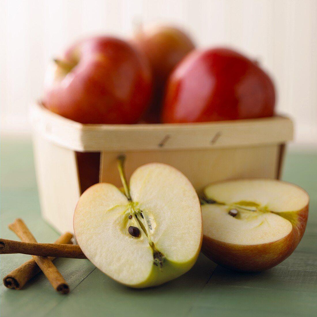 Apples in punnet, two apple halves & cinnamon sticks in front