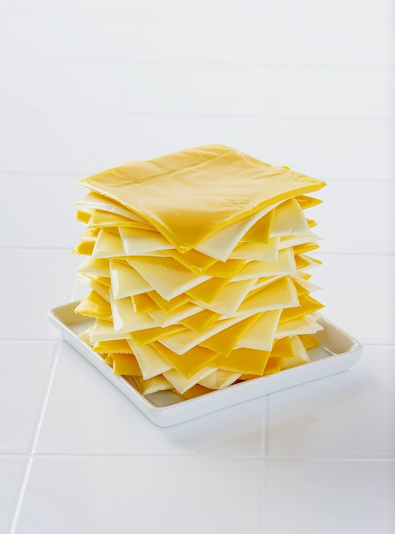 Slices of White and Orange American Cheese Piled High on a Dish