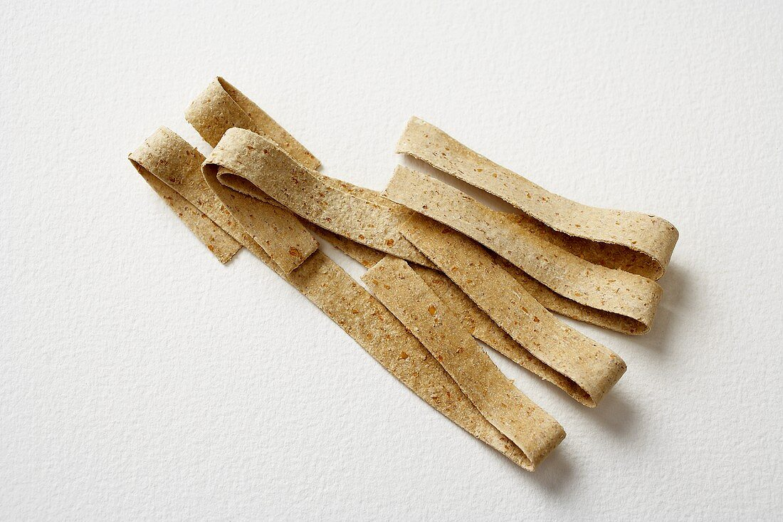 Organic Wheat Pasta on a White Background, Wide Noodles