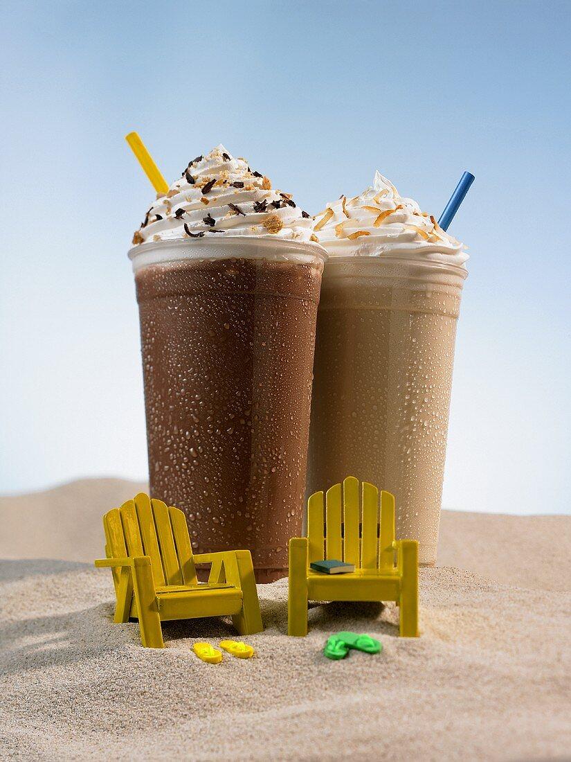 Chocolate milkshake and Coffee milkshake in the sand, two small chairs