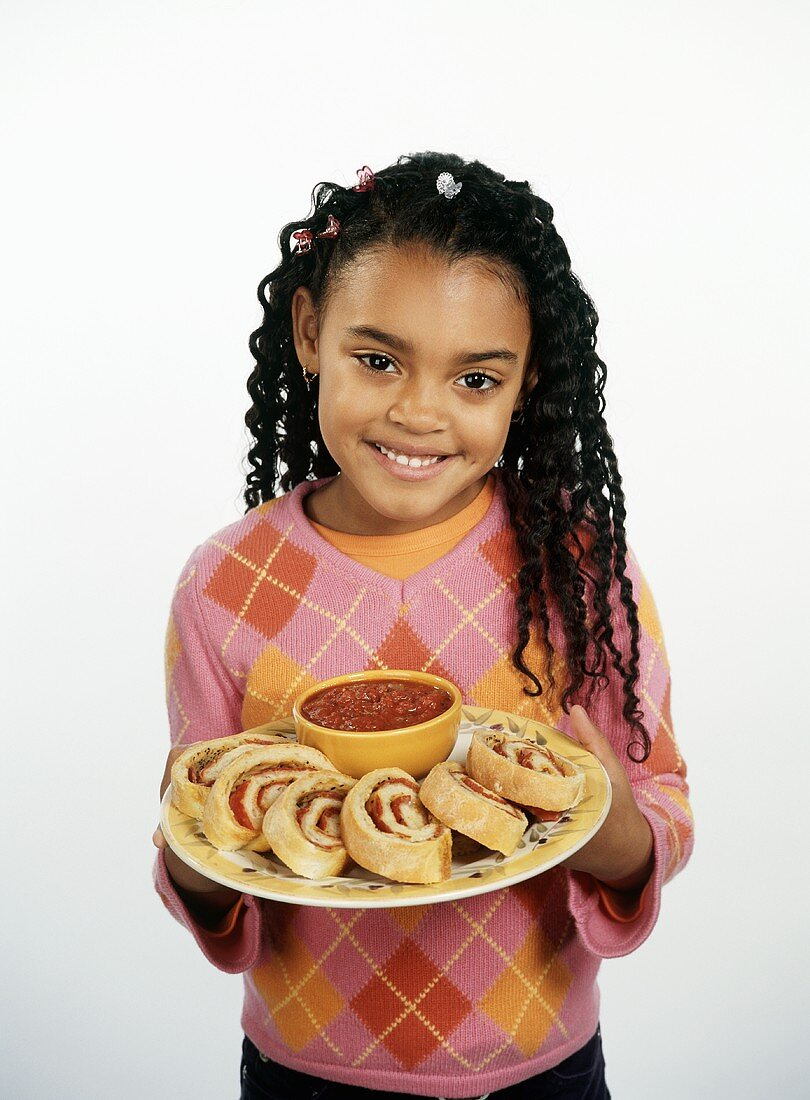 Young Girl Holding a Plate with Slices of Stromboli and a Bowl of Marinara Sauce