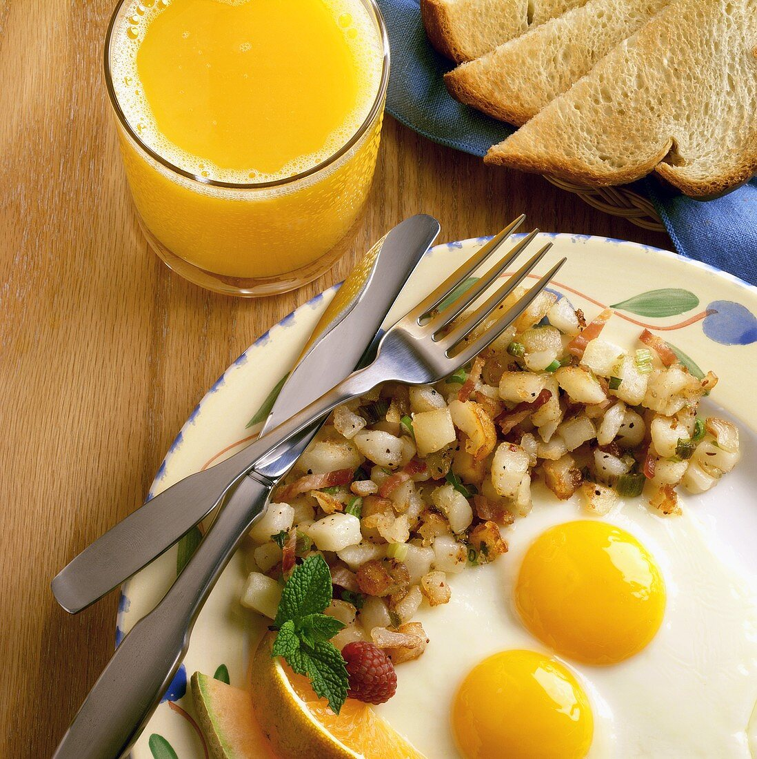 Two Fried Eggs with Hash Browns and a Glass of Orange Juice