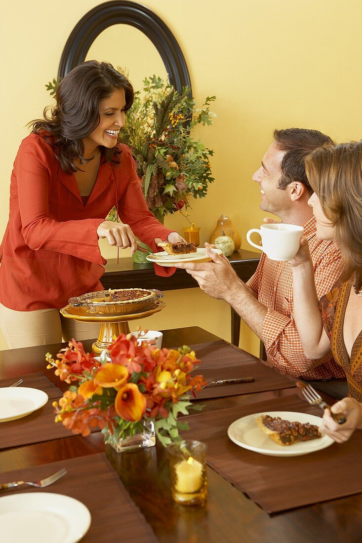 Woman Standing Serving Pie to Man at Thanksgiving Table, Woman Drinking Coffee and Eating Pie