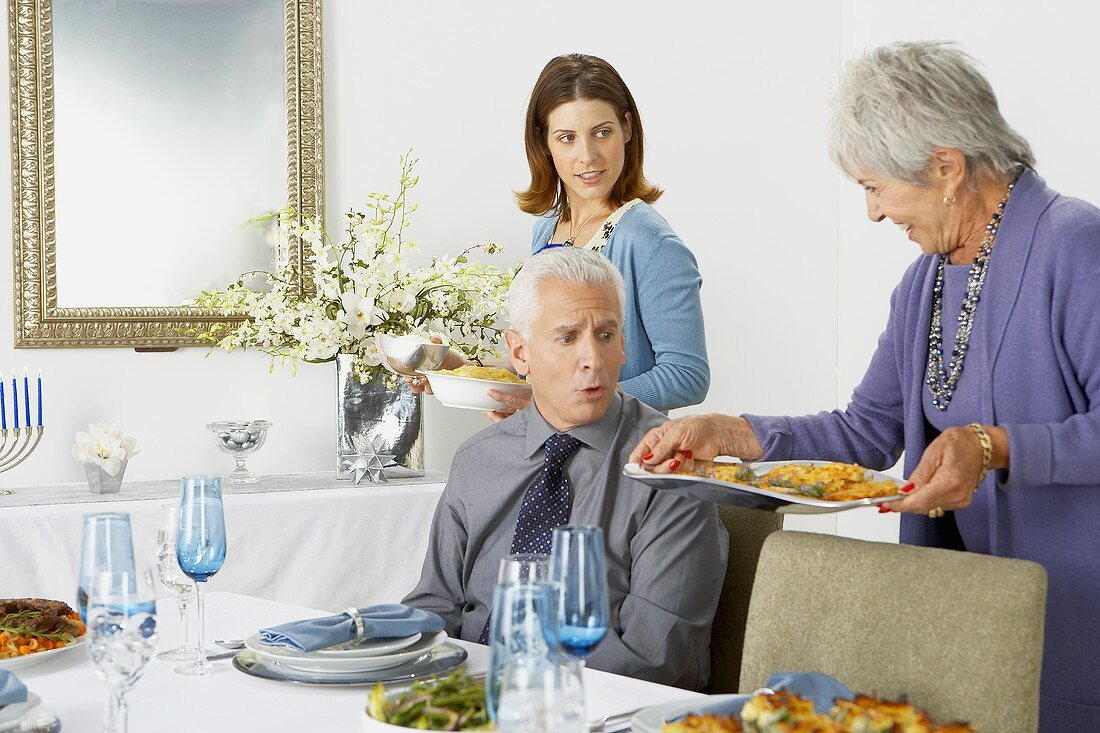 Women Bringing Hanukkah Meal to the Dining Table