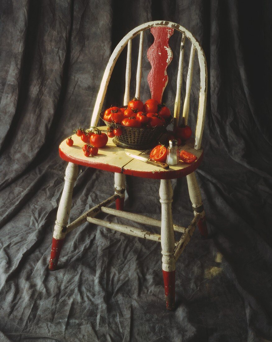 Freshly Washed Tomatoes in and Around a Colander on a Chair; Sliced Tomato with Salt and Knife