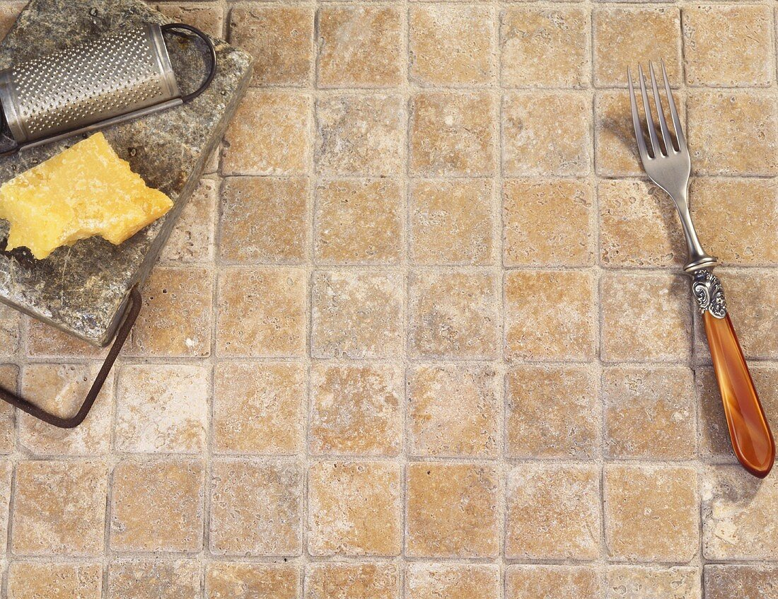 Piece of Parmesan Cheese with Grater on Stone Tiles; Fork
