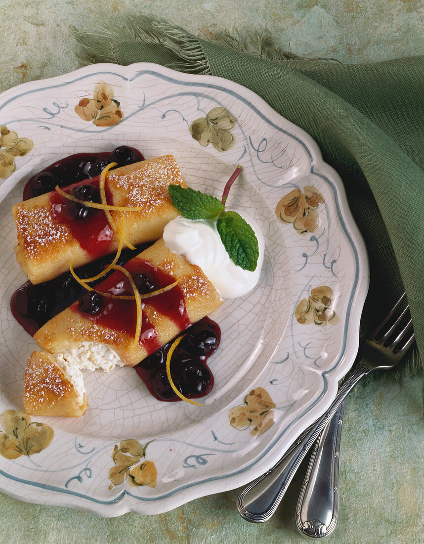 Serving of Cheese Blintzes Topped with Blueberry Sauce