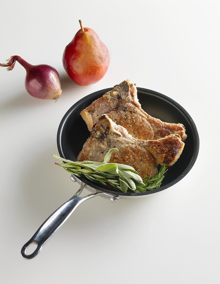 Pork Chops in a Skillet with Sage and Rosemary, a Pear and Onion on the Side