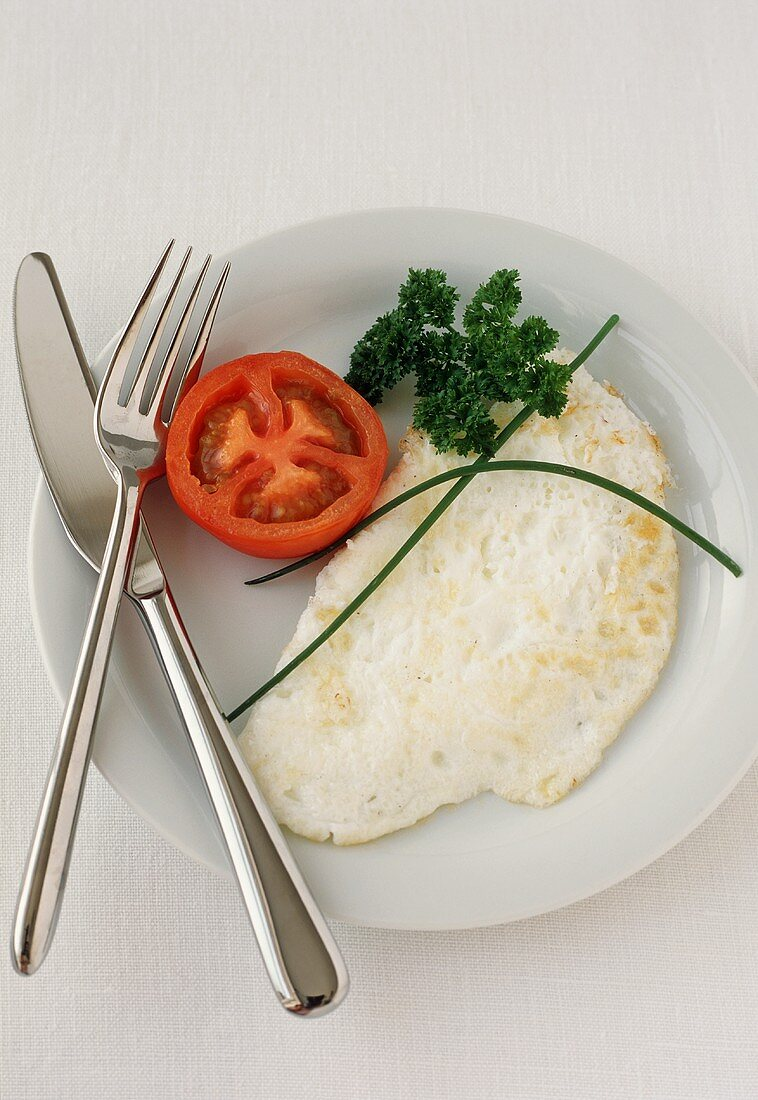 Egg White Omelet on a Plate with Fork and Knife and a Tomato