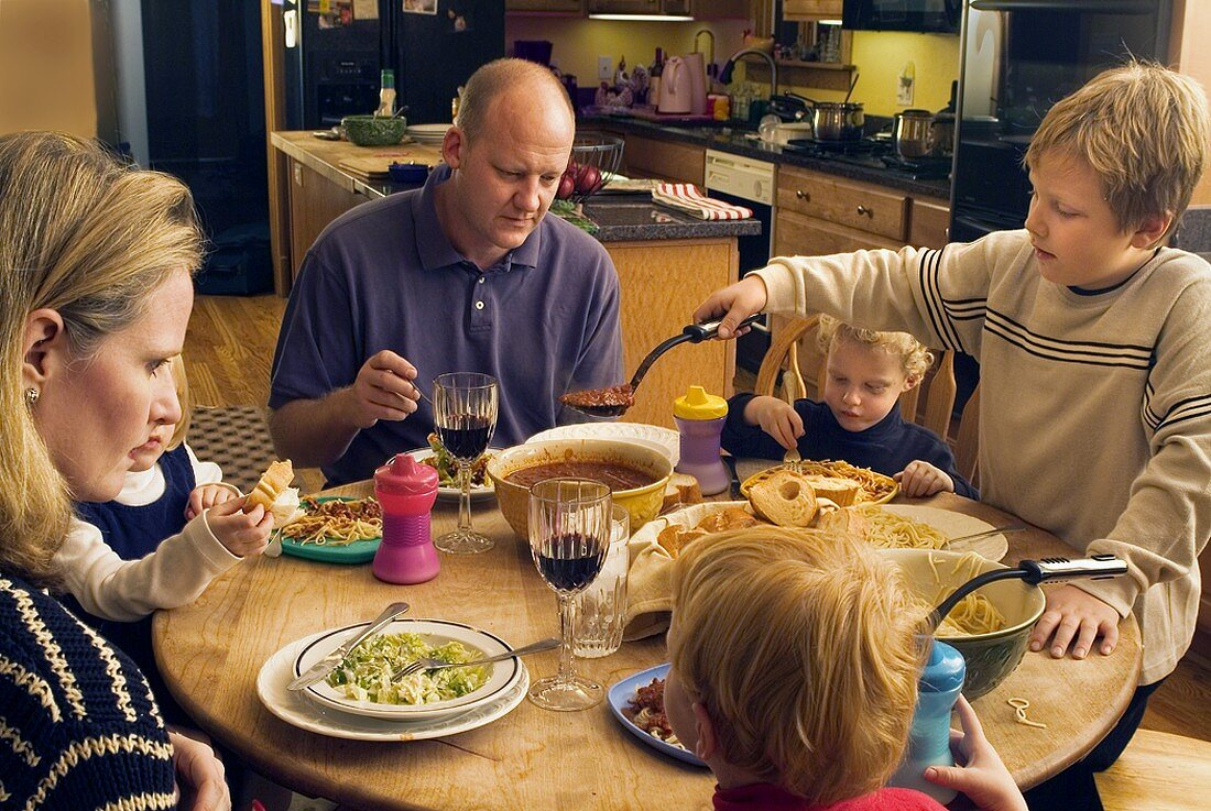 A Family Having Dinner of Spaghetti and Salad
