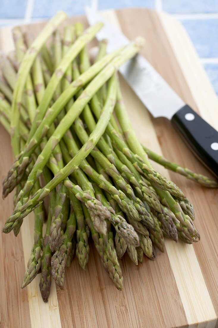Many Organic Asparagus Spears on a Cutting Board with a Knife