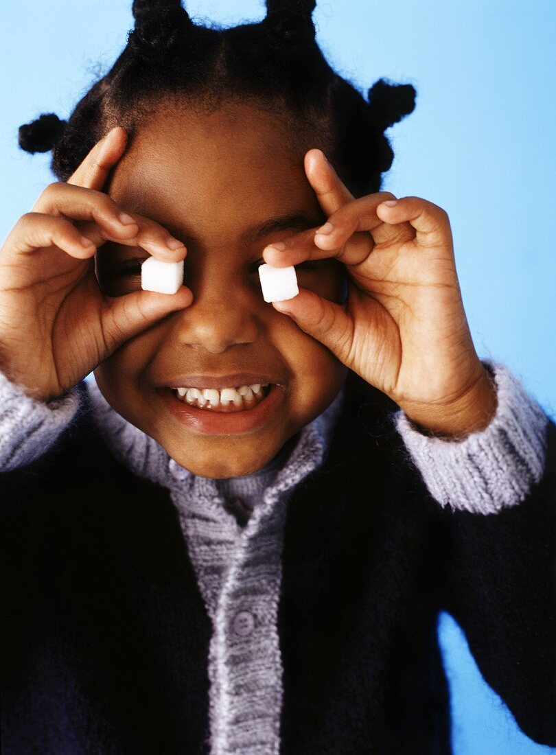 Girl holding sugar cubes in front of her eyes