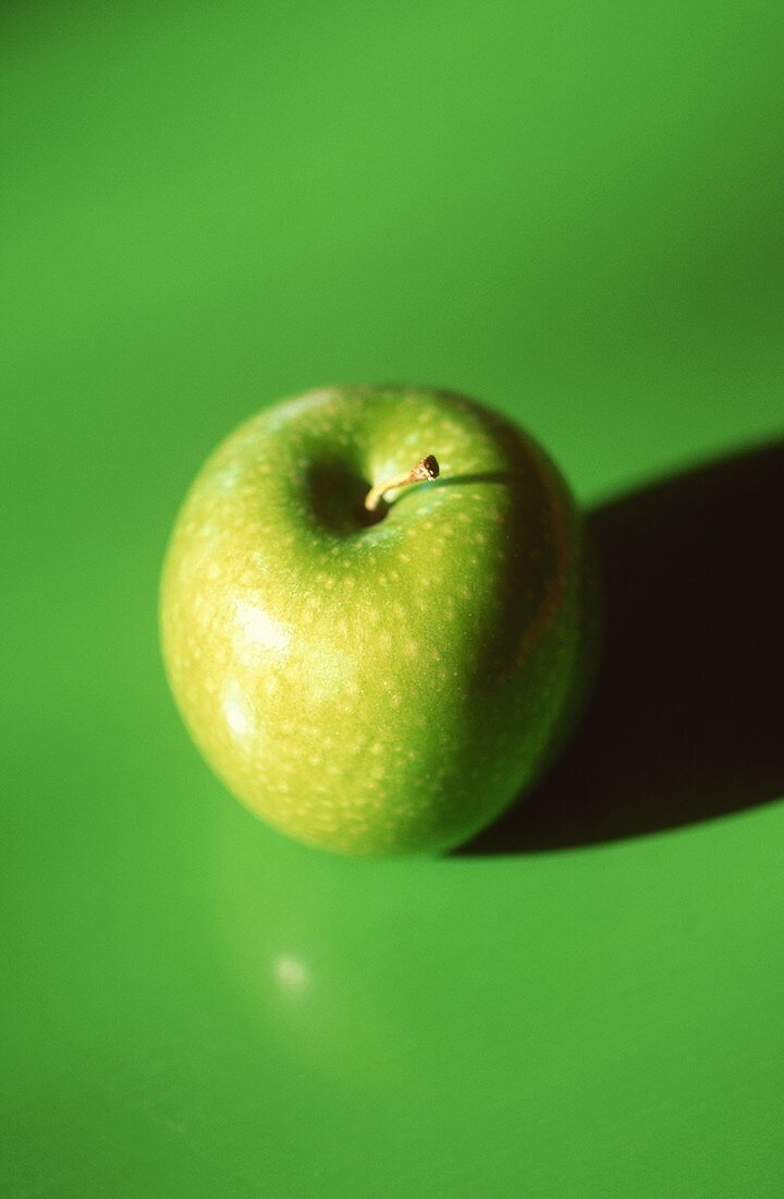 A Granny Smith apple on a green background