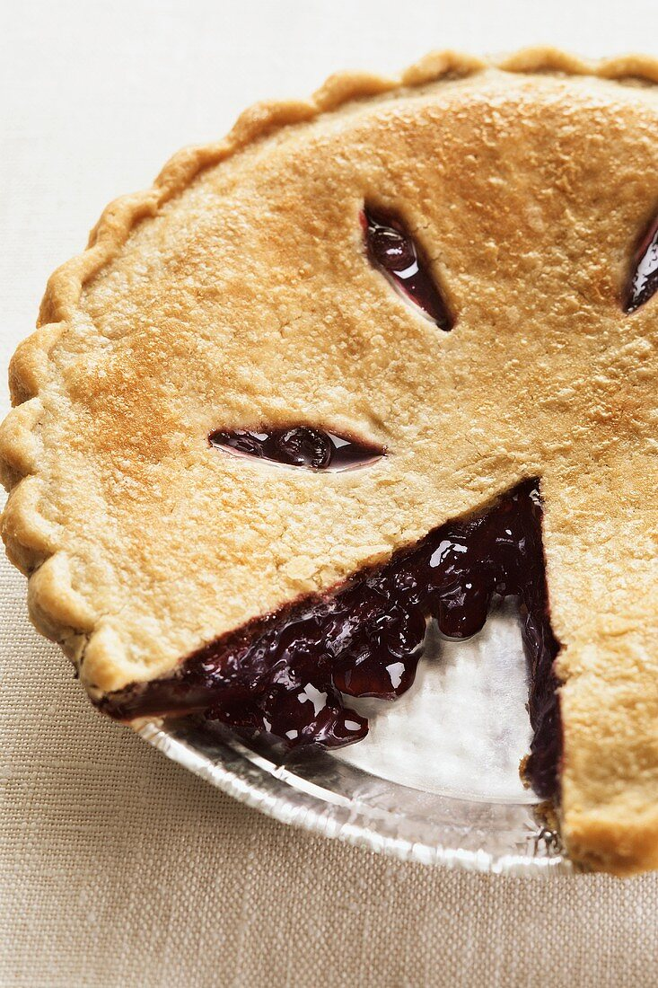 A Blueberry Pie with Slice Removed in a Foil Pan