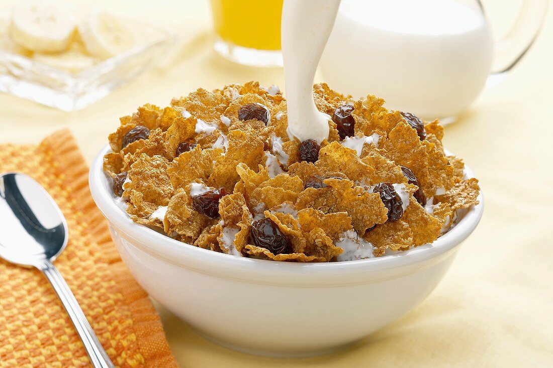 Pouring milk into a bowl of bran flake cereal with raisins