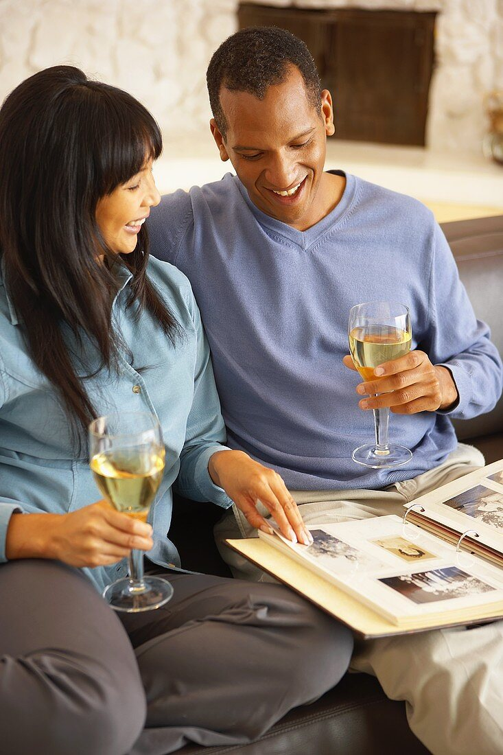 Couple on sofa drinking white wine & looking at photo album