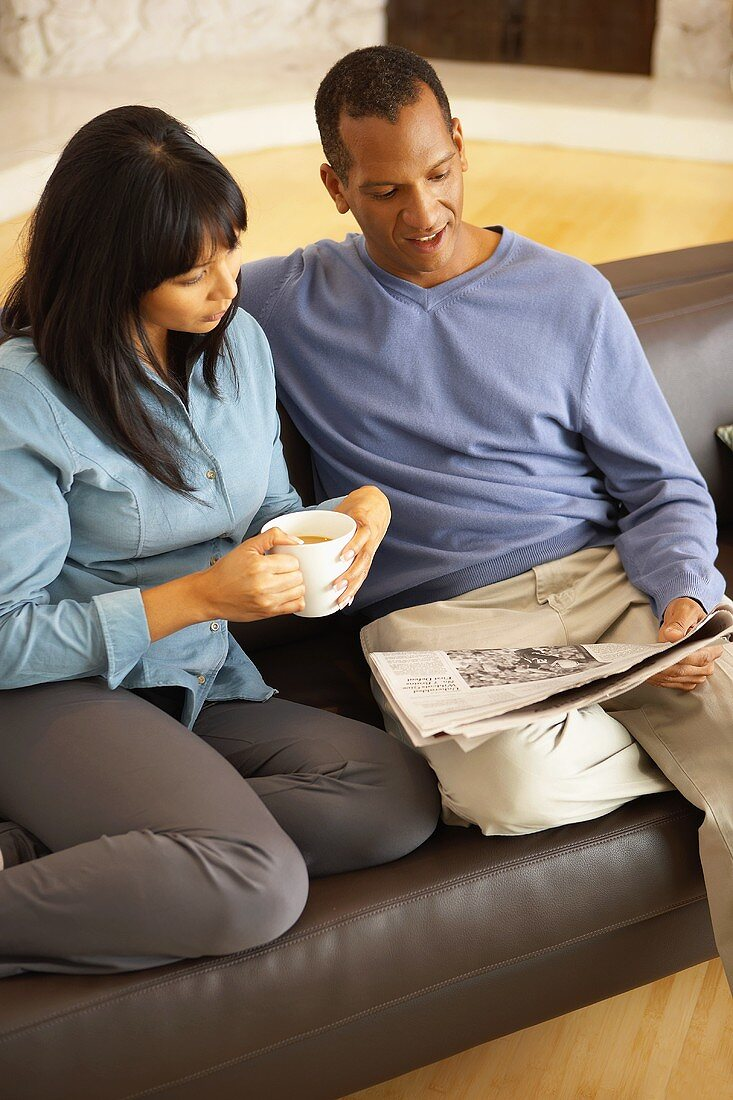 Woman with cup of coffee beside man with newspaper on sofa