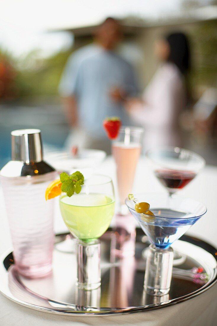 Verschiedene Cocktails mit Shaker auf Tablett im Freien