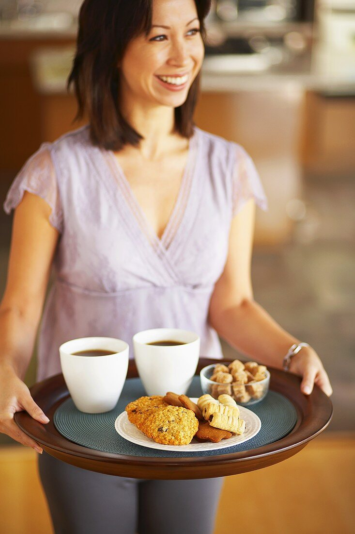 Woman carrying tray of coffee and biscuits