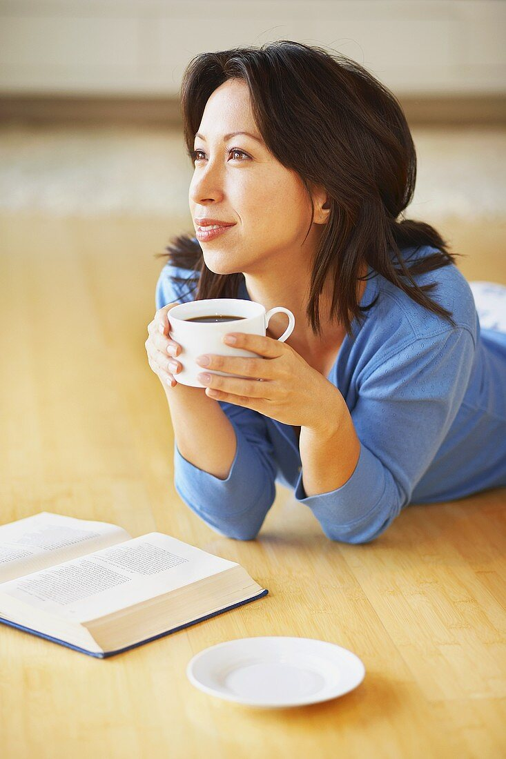 Woman with coffee and book (lying on the floor)
