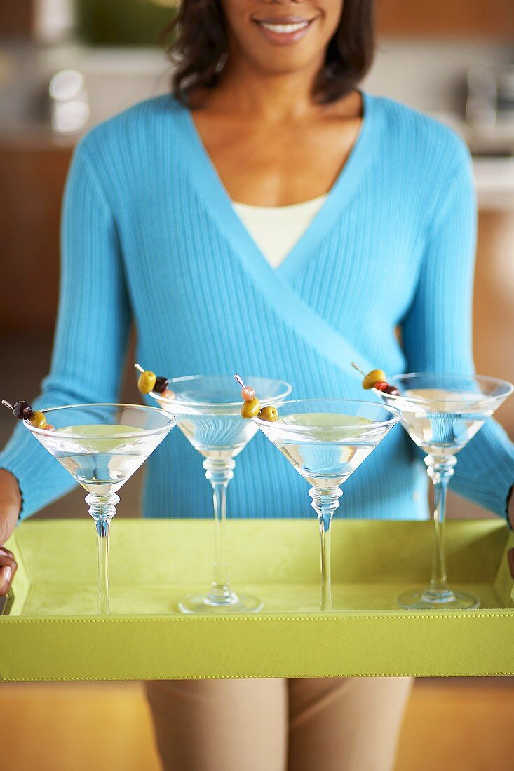 Woman carrying four Martinis on a tray