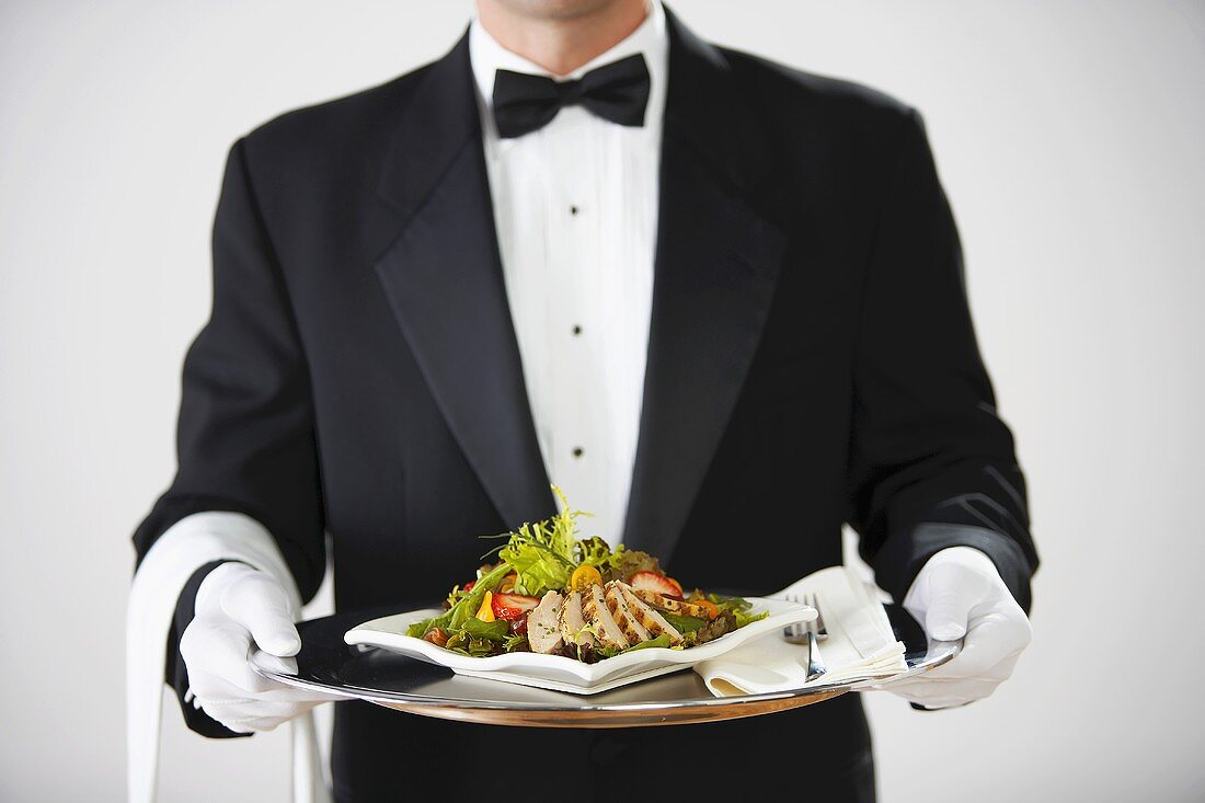 Butler serving chicken salad on silver tray